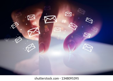 Finger touching tablet with white drawn mail icons above and dark background