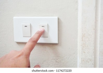 Finger trying to turn on switch of the lamp at the wall