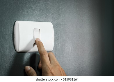 A finger turning on lighting switch on rough dark wall. Copy space.