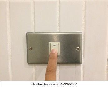 Finger turning on or off the light switch, switching off the light using as save energy concept.