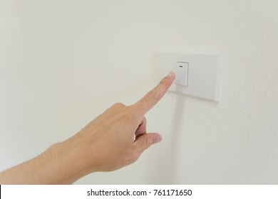 finger is turning on or off on light switch on walla. Copy space.