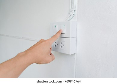 finger is turning on or off on light switch on walla. Copy space for text