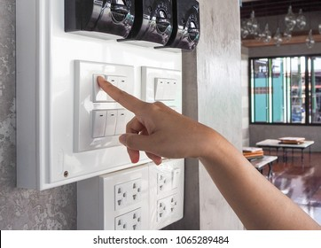 Finger is turning on one  light switch. Safe power concept.