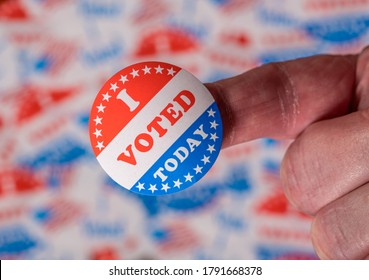 Finger with I Voted Today button in front of many voting stickers given to US voters in Presidential election to illustrate vote rights