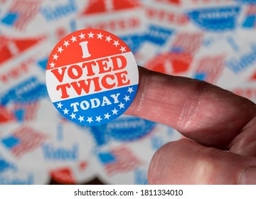 Finger with I Voted Twice button in front of many stickers given to US voters in Presidential election to illustrate vote fraud - Shutterstock ID 1811334010