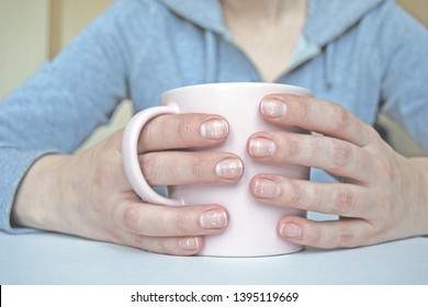 Fingernails with white dots and stripes, female hands holding pink mug, close-up
