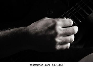 Fingerpicking on electric guitar; toned monochrome image