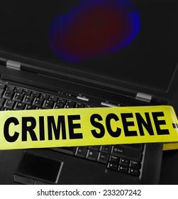 fingerprint on a laptop with crime scene tape