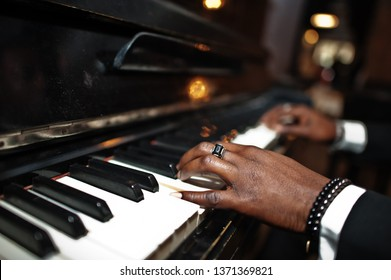 Fingers of african american man in black suit play piano.