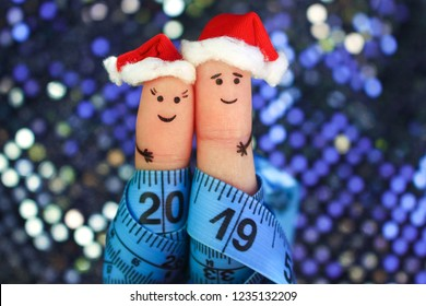 Fingers art of couple celebrates Christmas. Concept of man and woman laughing in New Year hats. Measuring tape is written 2019. Toned image.