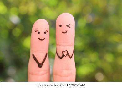 Fingers art of happy couple. Boyfriend showing fingers in heart shape. Concept of declaration of love.