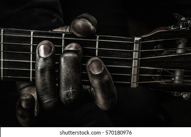 Fingers of blues:Fingers and strings in a close up, playing the guitar, making a tune.