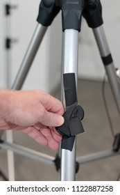 Fingers display camera remote control on tripodal. Hand holds camera remote control taped to a tripod Male hand showing camera remote control black gaff taped to a camera tripod in a tiled home office
