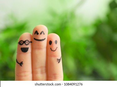 Fingers with drawings of happy faces against blurred background. Unity concept