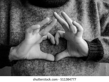 Fingers folded in the shape of a heart. The man in the sweater. Black and white.
