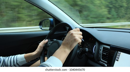 Fingers of driver's hands grip the steering wheel in car on the speed