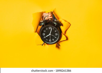 Fingers hold black retro alarm clock out of hole in torn yellow paper wall. No time to wait, good morning, wake up. Side for text and messages. Copy space.
