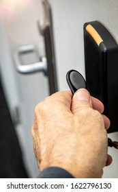 Fingers holding key fob on key fob sensor with door handle out of focus in the distance.