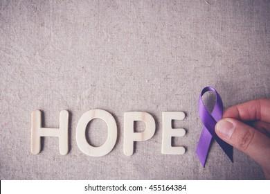 fingers holding Purple ribbon with HOPE wooden letter, toning, Alzheimer's disease, Pancreatic cancer, Epilepsy awareness, Hodgkin's Lymphoma awareness