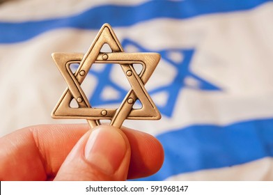 Fingers holding a Star of David (Magen David), Jewish traditional symbol, hexagram with a flag of Israel on the background. Jewish diaspora. Israel Independence Day. Conversion to judaism concept