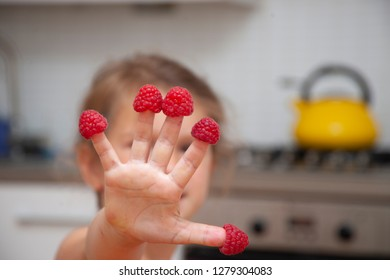 Fingers of the little girl with raspberry.