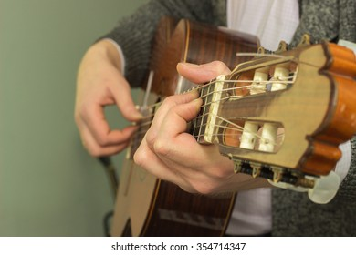 The fingers on the strings played with wooden guitar