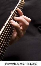 Fingers picking chord on acoustic guitar neck