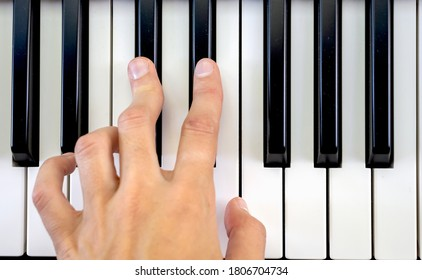 Fingers play chords on piano keys playing synthesizer pianist music hobby top view