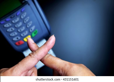 Fingers with sign of stop or danger above credit card machine/payment terminal insulated with card on black background. Focus on fingers. Dark tone.