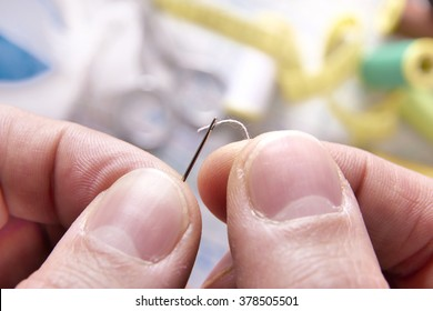 Fingers of a tailor threading a needle. Horizontal composition. Close up