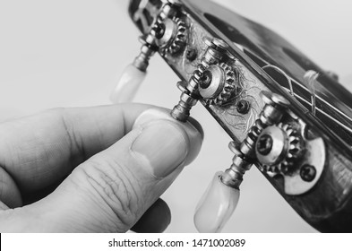 Fingers turning the tuning pegs and gears of the headstock of an acoustic guitar. Tuning the guitar. Details of the head of an old acoustic guitar. Black and white photo.