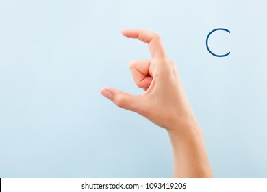 Fingerspelling alphabet. Female hands isolated on blue background showing deaf mute BSL alphabet letter C.