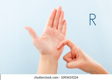 Fingerspelling alphabet. Female hands isolated on blue background showing deaf mute BSL alphabet letter R.