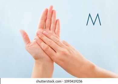 Fingerspelling alphabet. Female hands isolated on blue background showing deaf mute BSL alphabet letter M.