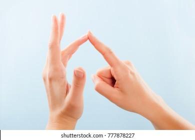 Fingerspelling alphabet. Female hands isolated on blue background showing deaf mute BSL alphabet letter O.