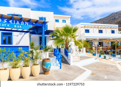 FINIKI, KARPATHOS ISLAND - SEP 30, 2018: Sculpture of Poseidon, god of the sea in ancient Greek religion and myth in front of typical Greek buildings in Finiki port, Karpathos island, Greece.
