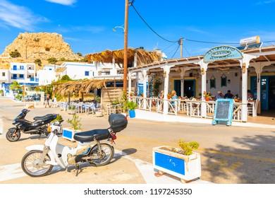 FINIKI PORT, KARPATHOS ISLAND - SEP 30, 2018: Scooters parking in front of typical Greek tavern on street of Finiki port, Karpathos island, Greece.