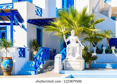 "FINIKI PORT, KARPATHOS ISLAND - SEP 25, 2018: Sculpture of ""Poseidon"" - god of the sea in ancient Greek religion and myth in front of typical buildings in Finiki port, Karpathos island, Greece."