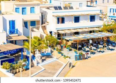 FINIKI PORT, KARPATHOS ISLAND - SEP 25, 2018: View of taverna restaurant and white houses in small fishing village on coast of Karpathos island, Greece.