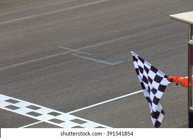 Finish line and checkered race flag in hand.