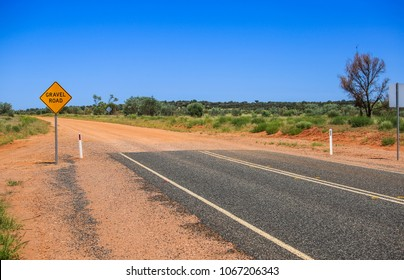 Finish of road. Yellow sign gravel road. Caution the end of a good road. Ended asphalt, beginning of off road terrain. Attention finish bitumen.