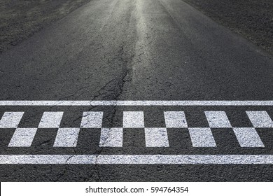 Finish and start pattern line on the sunny straight asphalt race road.