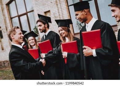 Finish Studies. Teacher. Students Diplomas. Courtyard. University. Graduate. Guys. Greet. Group of Young People. Good Mood. Have Fun. Friendship. Knowledge. Cap. Cheerful. Celebration.