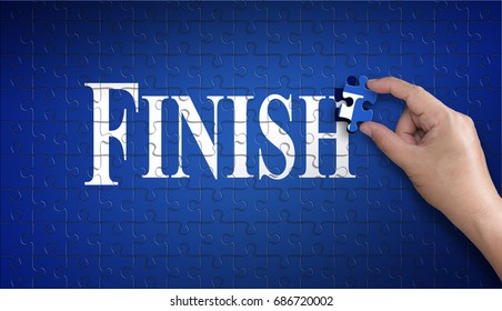 Finish word on Jigsaw puzzle - business concept. Man hand holding a blue puzzle to complete the word Finish divided over them concept of the solution to a problem, challenge, plan and strategy.