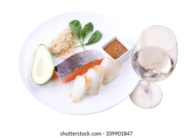 The finished dish with a side dish of seafood and fresh vegetables on a white plate with a glass of wine  isolated on white background