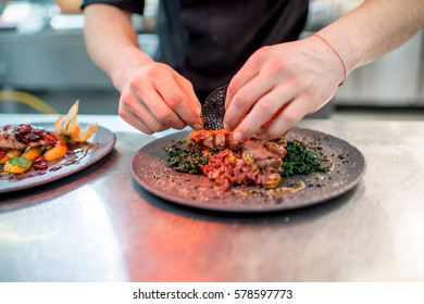 Finishing delicious restaurant dish with meat on the restaurant kitchen