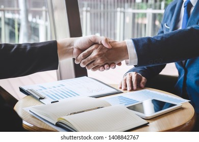 Finishing up a meeting, handshake of two happy business people after contract agreement to become a partner, collaborative teamwork.
