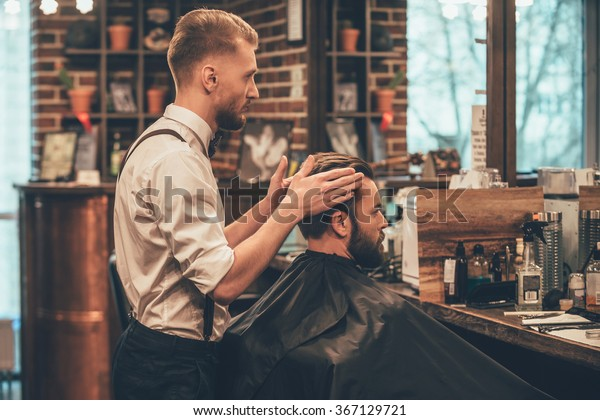 Finishing touch. Side view of hairdresser checking symmetry of haircut of his client at barbershop