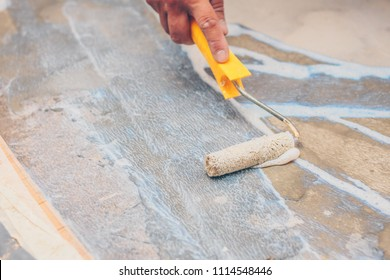 finishing works - a working roller primer floors for laying tiles