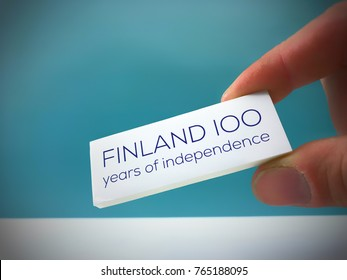 Finland celebrating 100 years of independence in 6th December 2017. Fingers holding white card with Finland 100 years of independence text. Suomi 100